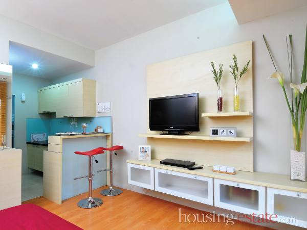 Dapur dan meja sarapan dekan pintu masuk. Desain kabinet TV dengan laci-laci melayang di depan tempat tidur.