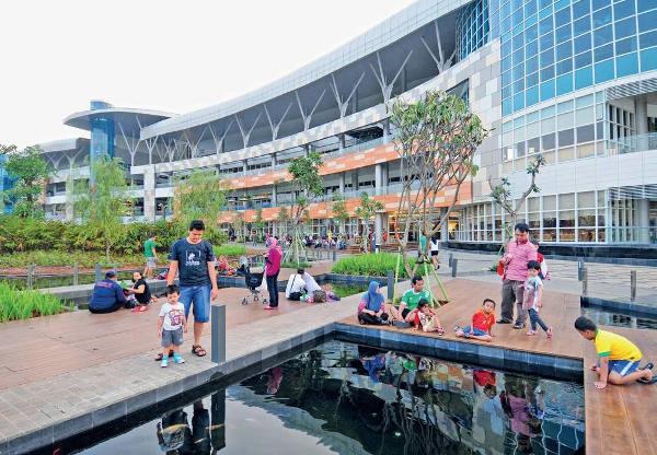 Pengunjung menikmati kolam koi di taman