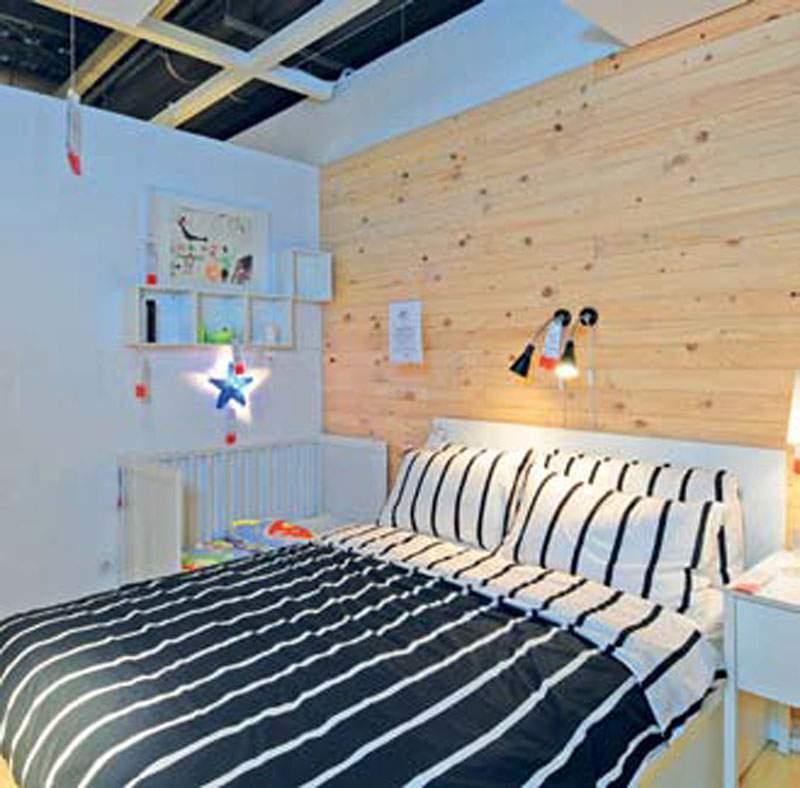 Kamar Tidur Utama Kamar tidur utama diberi aksen dinding kayu cokelat untuk memberi kesan hangat. Tata letak tempat tidur utama berdampingan dengan boks bayi yang mengisi sudut ruang. Area ranjang terbuka ke kamar mandi dan dapat menembus ke area kamar tidur anak untuk memudahkan pengawasan.