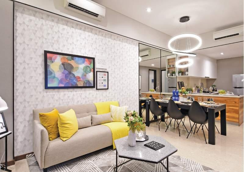 Aksen kuning mencerahkan sudut ruang keluarga dengan dekorasi motif geometris pada dinding